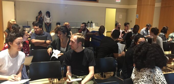 Photo of an interactive workshop at the CUNY Graduate Center. Several pairs of people sit together, sharing paper documents and talking