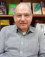 Photo of David Olan sitting in front of book shelf