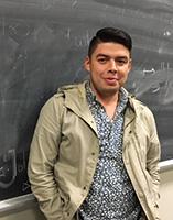José Alfredo Menjívar standing in front of a chalkboard