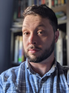 Profile photo of Travis Bartley sitting in front of a bookshelf