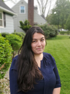 Profile photo of Meagan Hammerbacher standing on a green lawn in front of a house