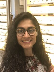 Profile photo of Mehrnaz Moghaddam in front of lit cases holding eye glasses.